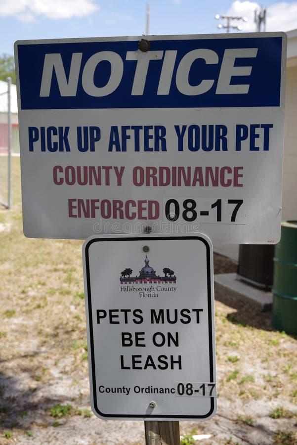 Offentligt älsklings- meddelande som säger att plocka upp efter ditt husdjur royaltyfria foton