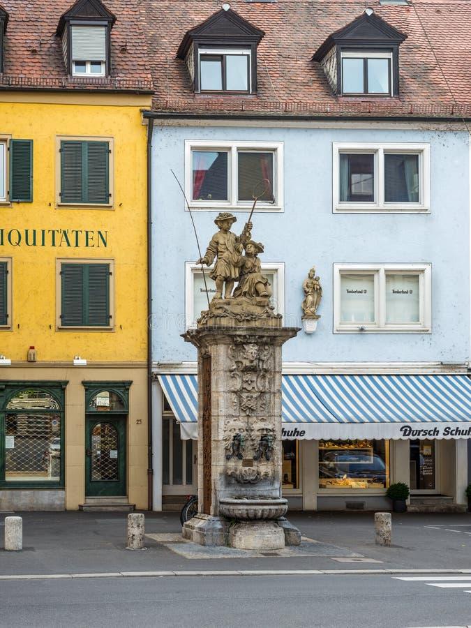 Offentligt gammalt dricksvattenklapp med statyn på gatan i Wurzb fotografering för bildbyråer