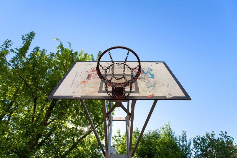 Offentligt utomhus- beslag för basketdomstol, med träd i bakgrunden och en solig blå himmel royaltyfri bild