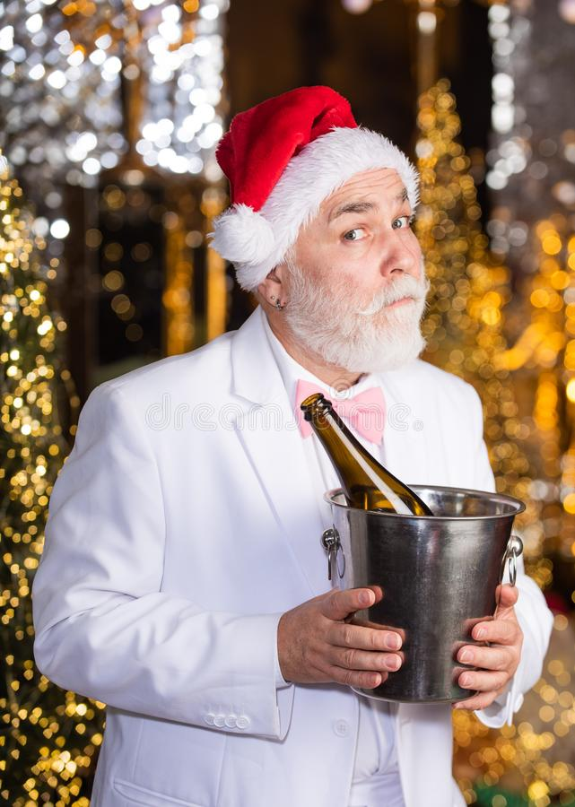Offer chilled good wine. tuxedo senior sommelier. new year night might be long. merry christmas to you. lets celebrate. Cheerful man hold ice bucket with stock image