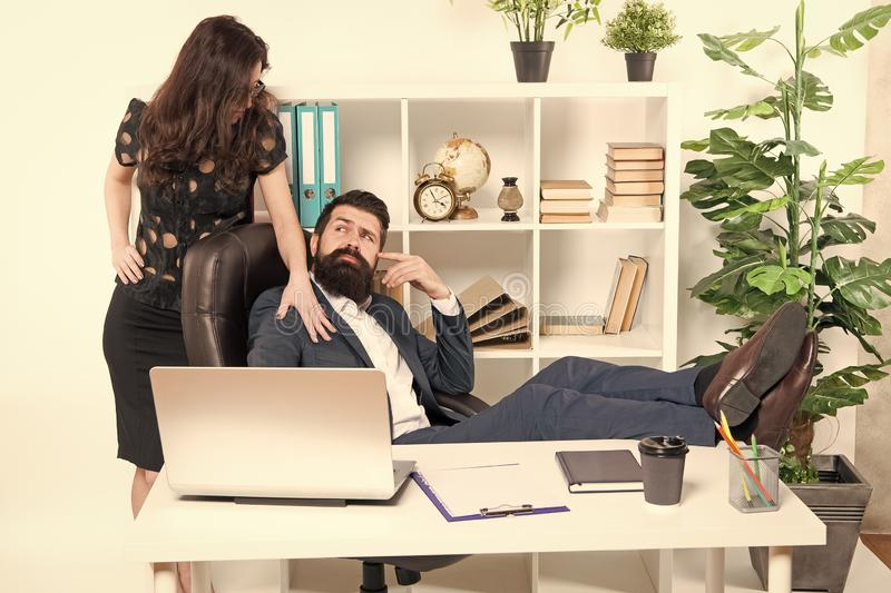 Offer massage. Man bearded hipster boss sit in leather armchair office interior. Boss and secretary girl at workplace royalty free stock photo