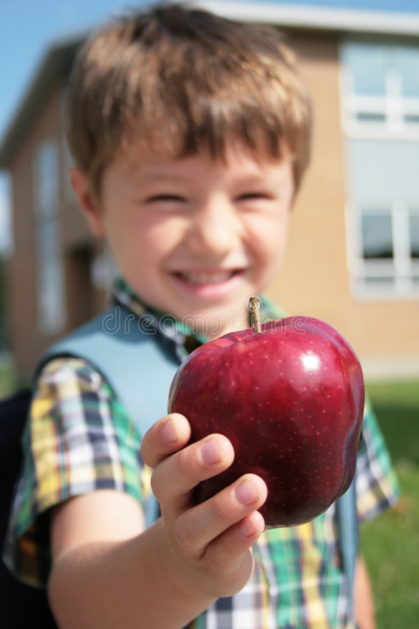 Offering an apple. Young smiling boy offering an apple stock images