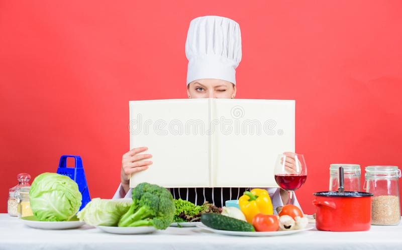 Offering balanced menu. Adorable woman learning restaurant menu for a day. Pretty female cook reading menu card at stock image