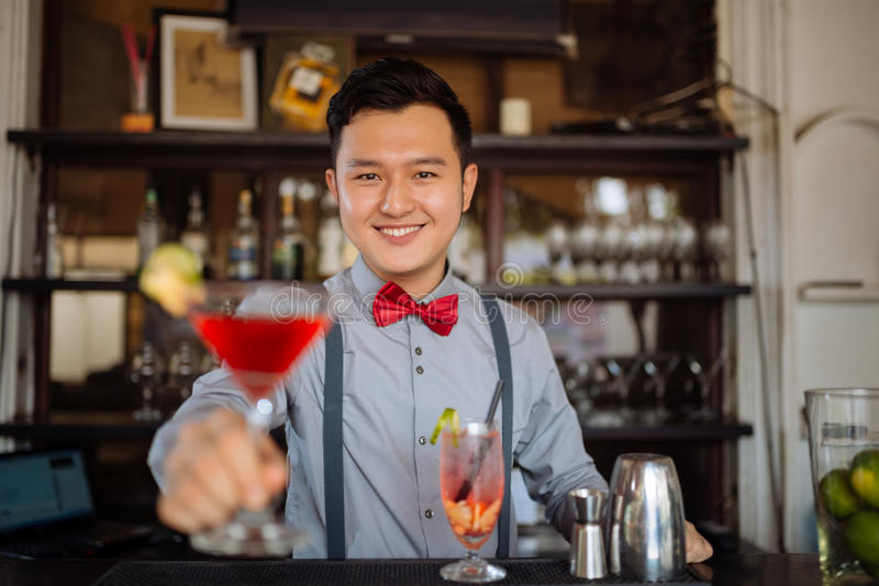 Offering a cocktail. Portrait of smiling handsome bartender offering a cocktail royalty free stock photos