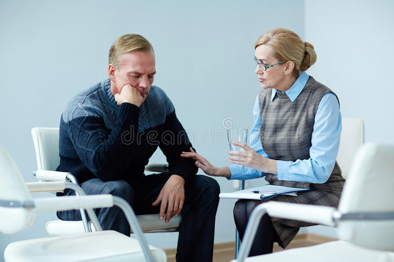 Offering glass of water. Mature psychiatrist offering glass of water to despaired man royalty free stock photos
