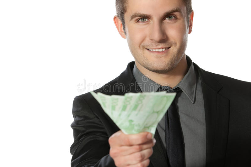 Offering money. Young business man offering pack of Euro money over white background royalty free stock photos