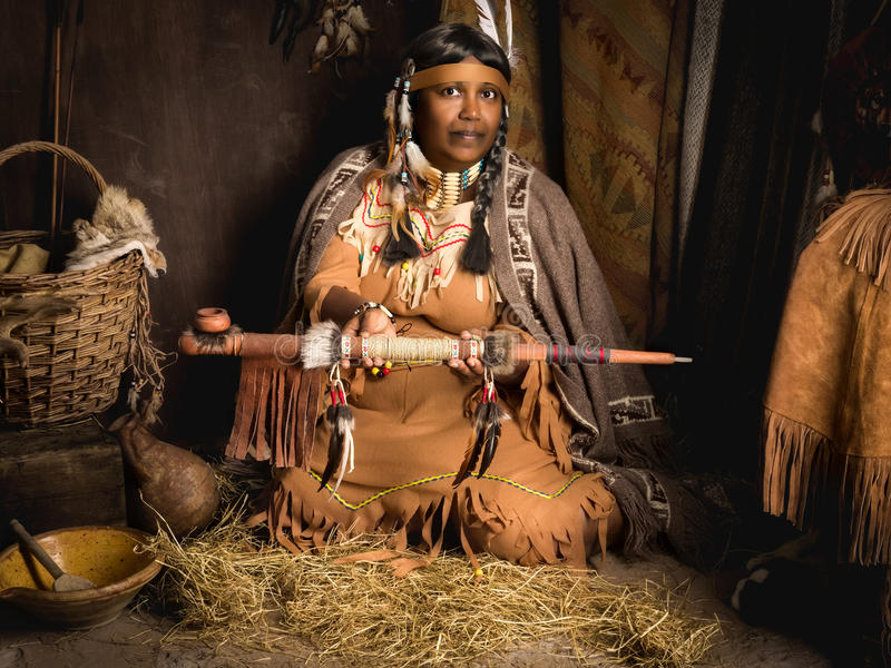 Offering peace pipe. Weathered mature tribal female storyteller talking about heroic times royalty free stock photography