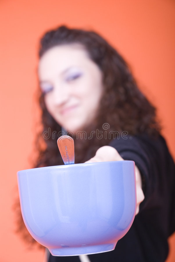 Offering tea. Young woman holding a cup and offering a teacup royalty free stock photography