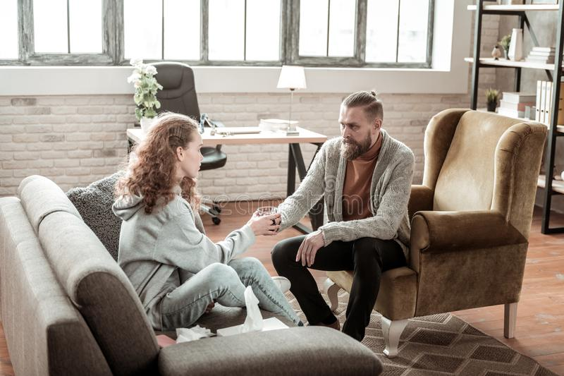Bearded private counselor offering glass of water to his client. Offering water. Bearded private counselor offering glass of water to his client sitting in front royalty free stock image