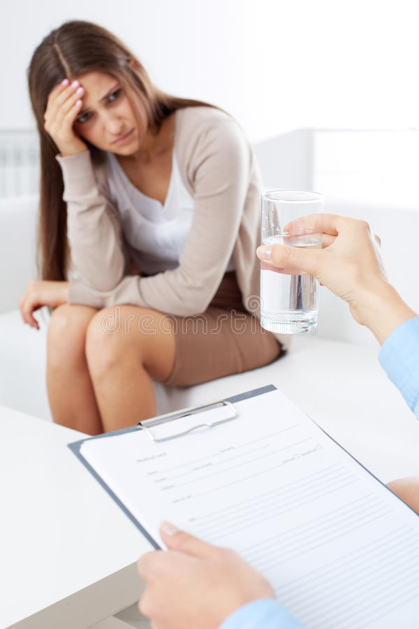 Offering water. Upset patient sitting on psychiatrist couch while doctor offering her a glass of water stock photos