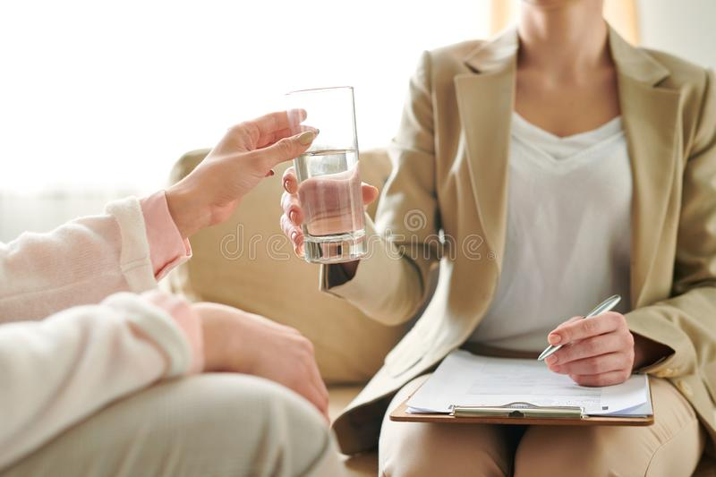 Offering water. Young patient taking glass of water from hand of her counselor during individual session stock images