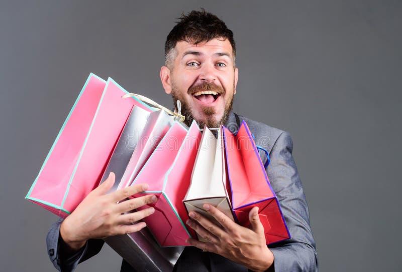 Offerta commerciale esclusiva Il cliente barbuto dell'uomo d'affari dell'uomo porta molti sacchetti della spesa Goda degli affari immagine stock libera da diritti
