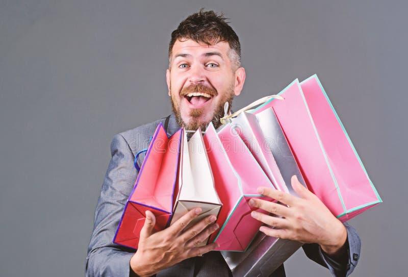 Offerta commerciale esclusiva Il cliente barbuto dell'uomo d'affari dell'uomo porta molti sacchetti della spesa Goda degli affari fotografie stock