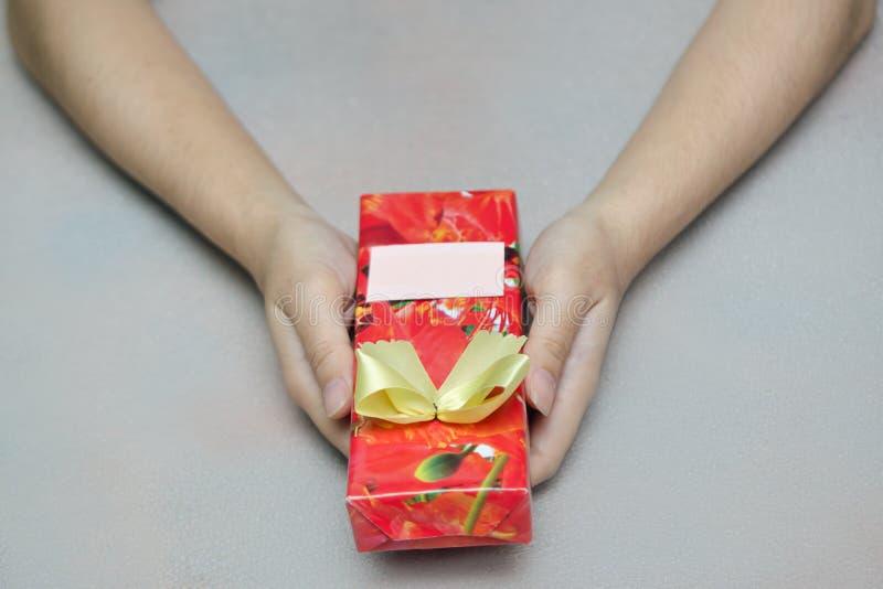 Offerta del contenitore di regalo presente con la mano che tiene, il Natale e Ne immagine stock libera da diritti