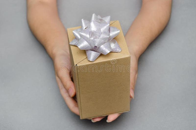 Offerta del contenitore di regalo presente con la mano che tiene, il Natale e Ne fotografia stock