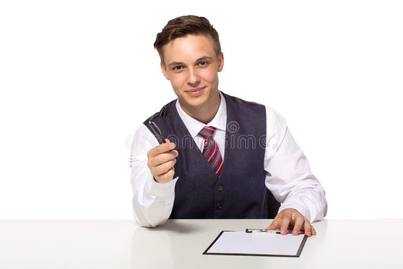 Offerte sorridenti dell'uomo d'affari o del responsabile per firmare un contratto che tiene una penna ed i documenti per la firma fotografie stock libere da diritti