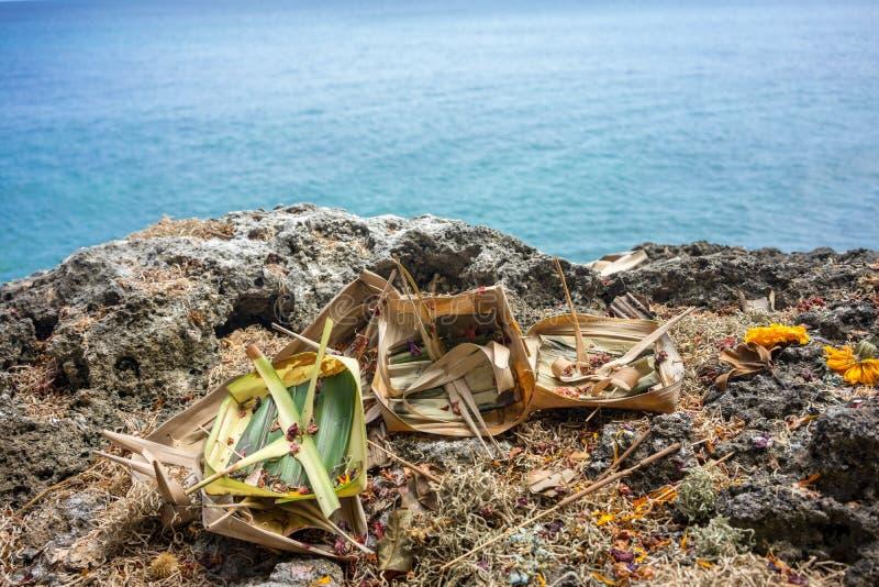 Offerti indù e regali al dio sulla scogliera davanti all'oceano in Bali, Indonesia immagini stock