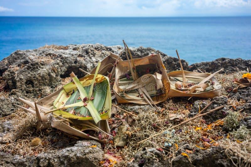 Offerti indù e regali al dio sulla scogliera davanti all'oceano in Bali, Indonesia fotografia stock libera da diritti