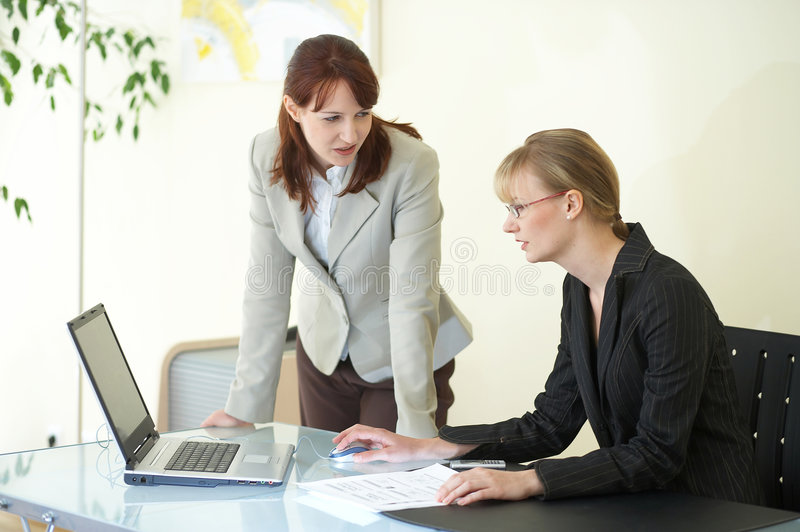 In the office. Two businesswomen are discussing the work stock photo