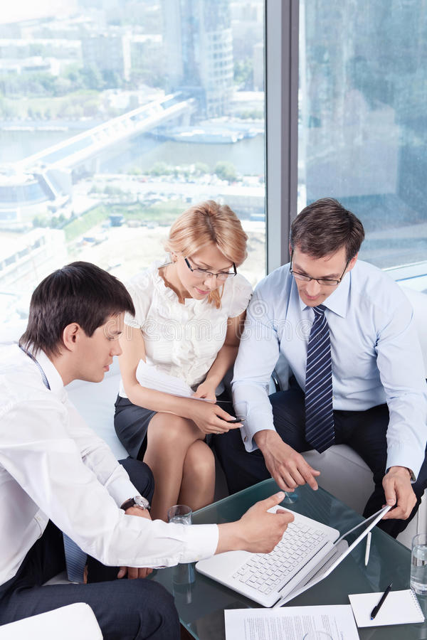 In the office. Business people looking at laptop royalty free stock photo