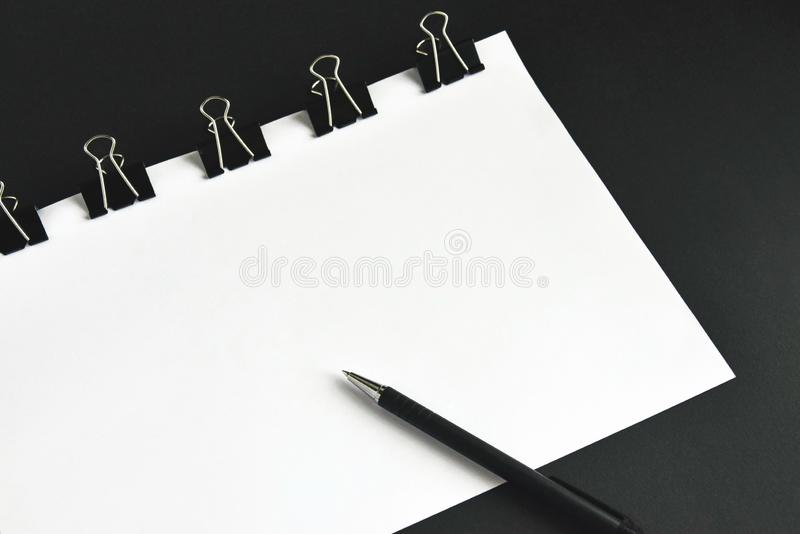 Office accessories, white sheets, pen and binder clip royalty free stock images