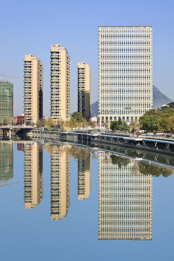Office and apartment buildings reflected in a blue canal, Hengdian, China royalty free stock images