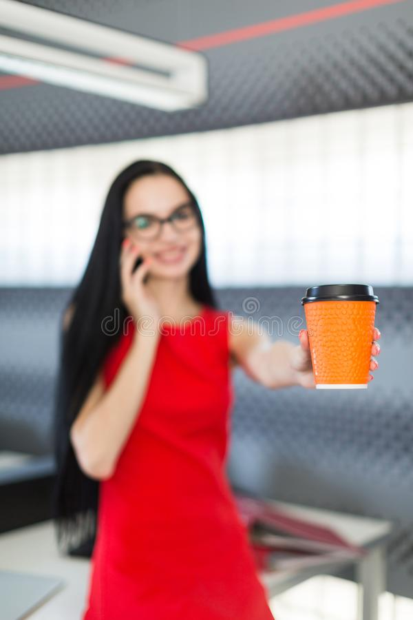 Beautiful young businesswoman in red dress and glasses sit on table in the office and hold coffe cup stock photography