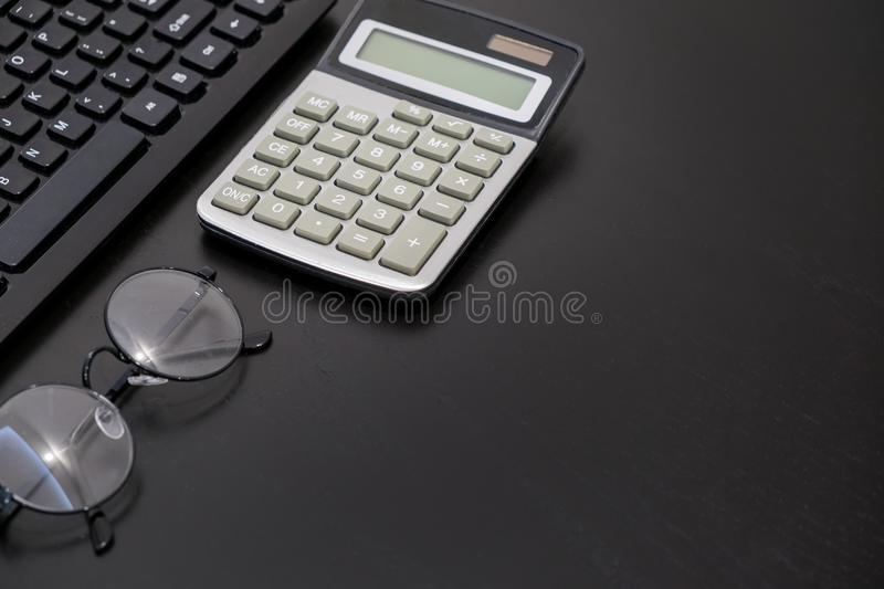 Office black Desk table with computer, calculator, smartphone, glasses, pan, supplies. Top view with copy space stock photos