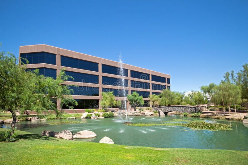 Office Building. Water fountain in pond in front of an office building stock photo