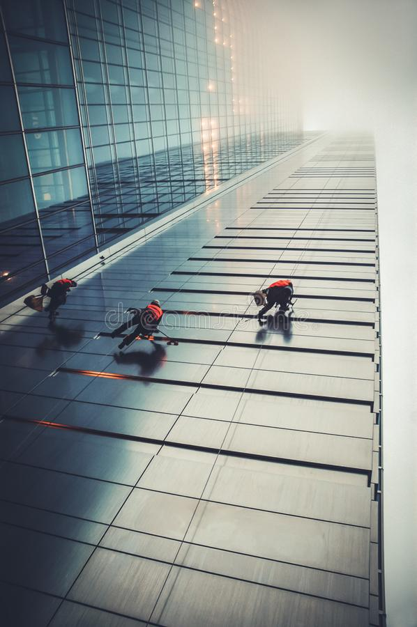 Office building cleaners in Warsaw. Warsaw, Poland - November 28, 2006: Window cleaners on a Rondo 1 office skyscraper located at Rondo ONZ in Warsaw city royalty free stock image