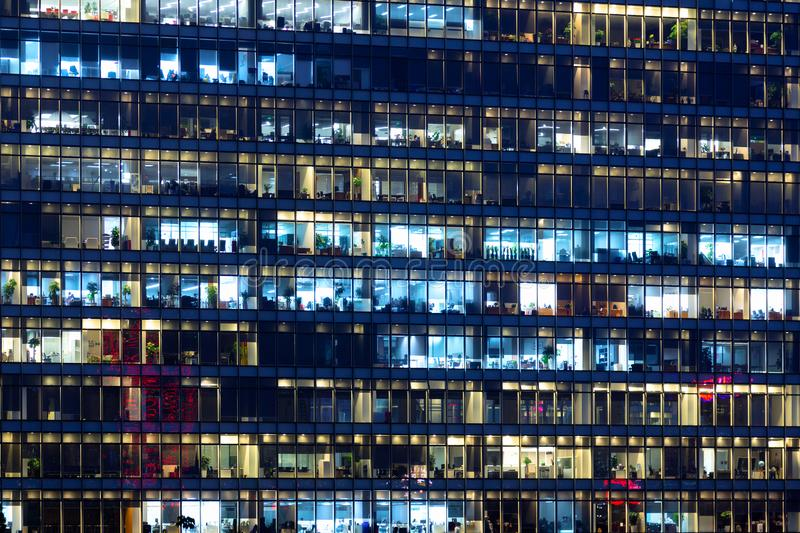Office building exterior in the late evening with interior lights. Business people working in the evening. Illuminated office royalty free stock photography