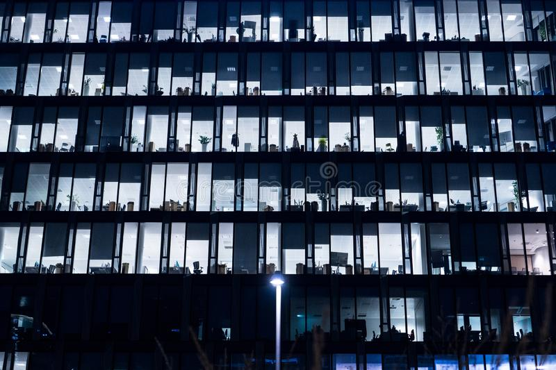 Office Building At Night. Late night at work. Glass curtain wall office building. Office building exterior in the late evening stock image