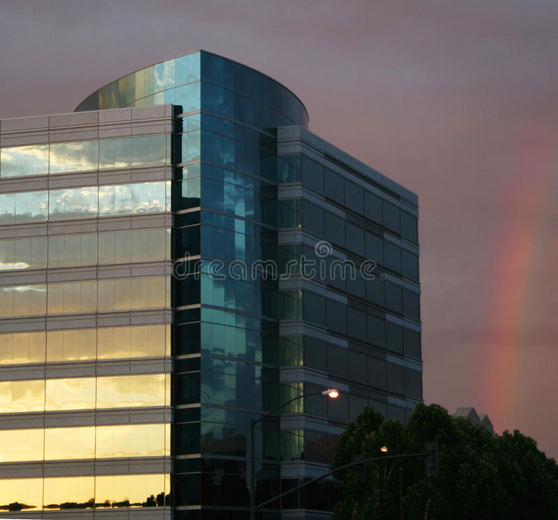 Office building and rainbow stock image