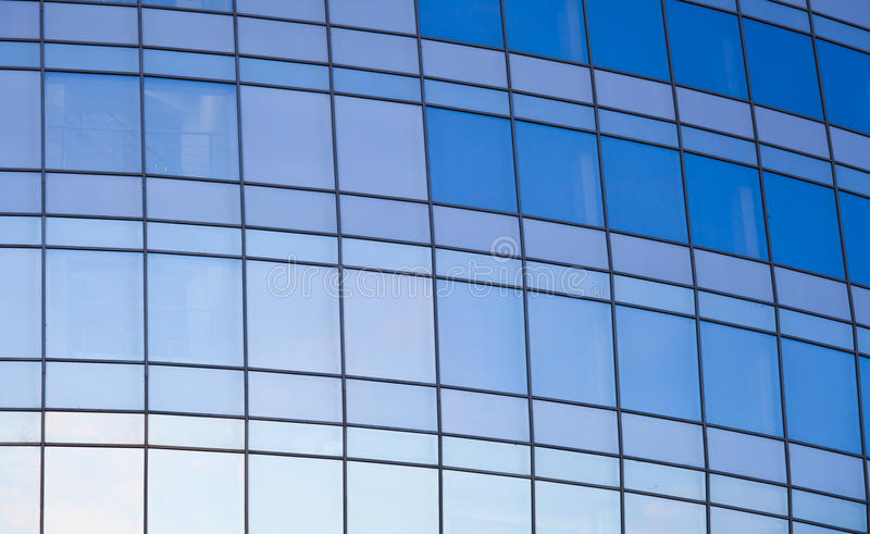 Office building wall made of mirrored blue glass royalty free stock photography