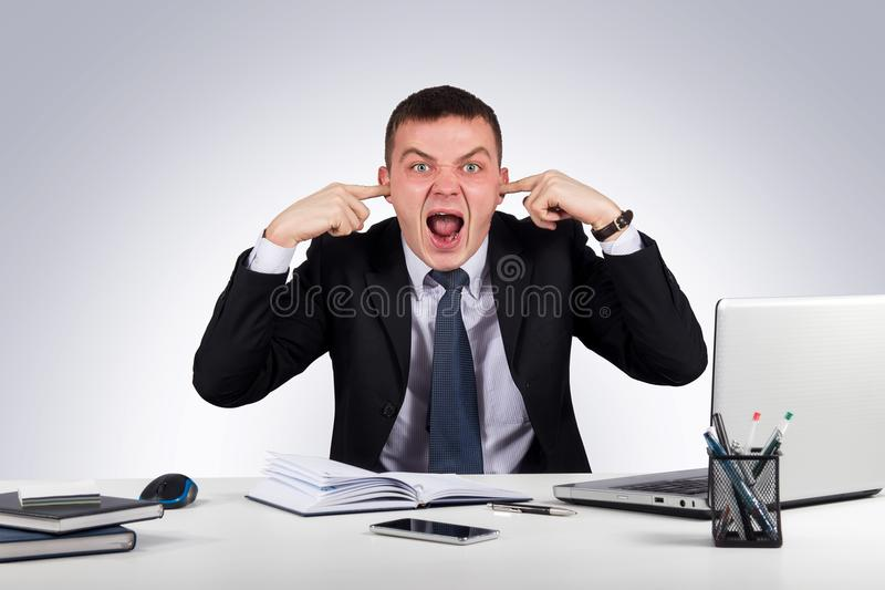 Office, business, technology, finances and internet concept-Young businessman shuts his ears with his hands and screaming stock photo