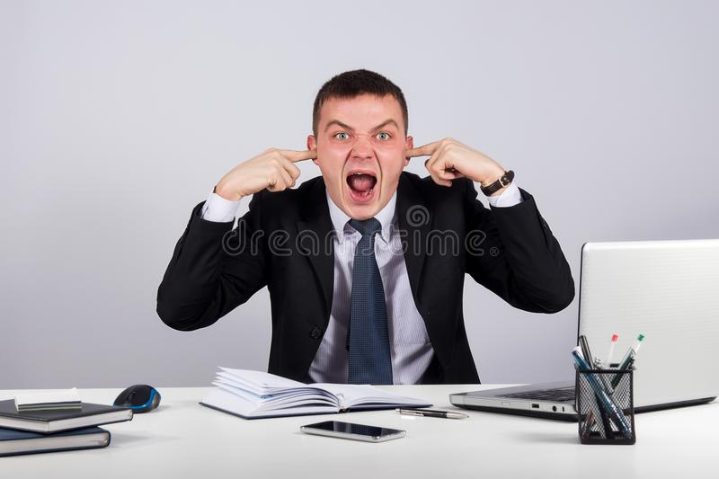 Office, business, technology, finances and internet concept-Young businessman shuts his ears with his hands and screaming stock image