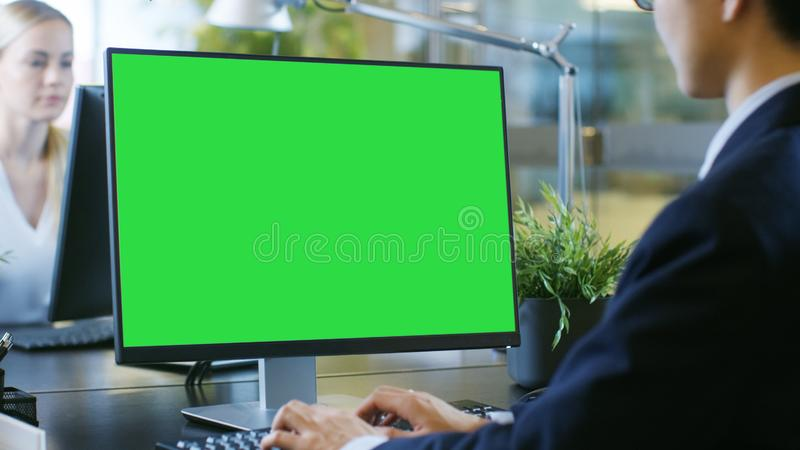 In the Office Businessman works at His Desk on a Personal Computer with Mock-up Green Screen. His Colleague Sets Opposite to Him. stock images