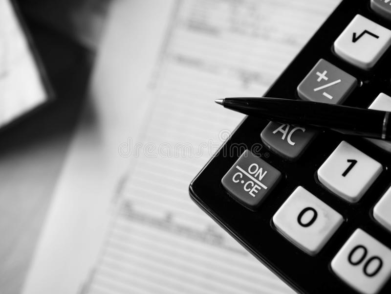 Office calculator and a pen over documents close up shot in black and white. Space for text royalty free stock images