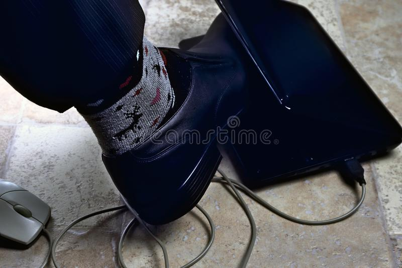 Office clerk`s foot is clamped in netbook as in trap, overwork, work seven days a week stock photos