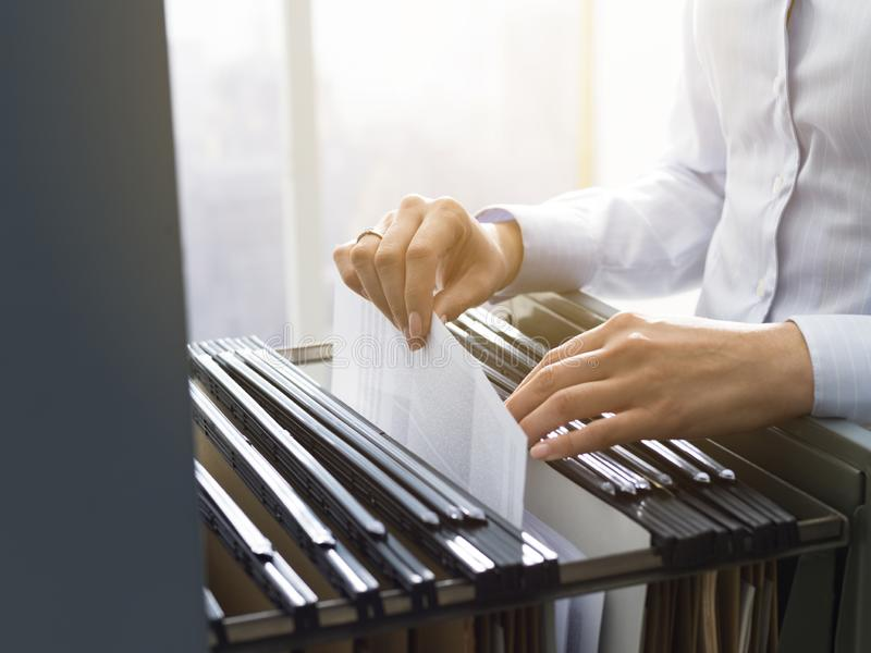 Office clerk searching files in the filing cabinet. Professional female office clerk searching files and paperwork in the filing cabinet stock photos