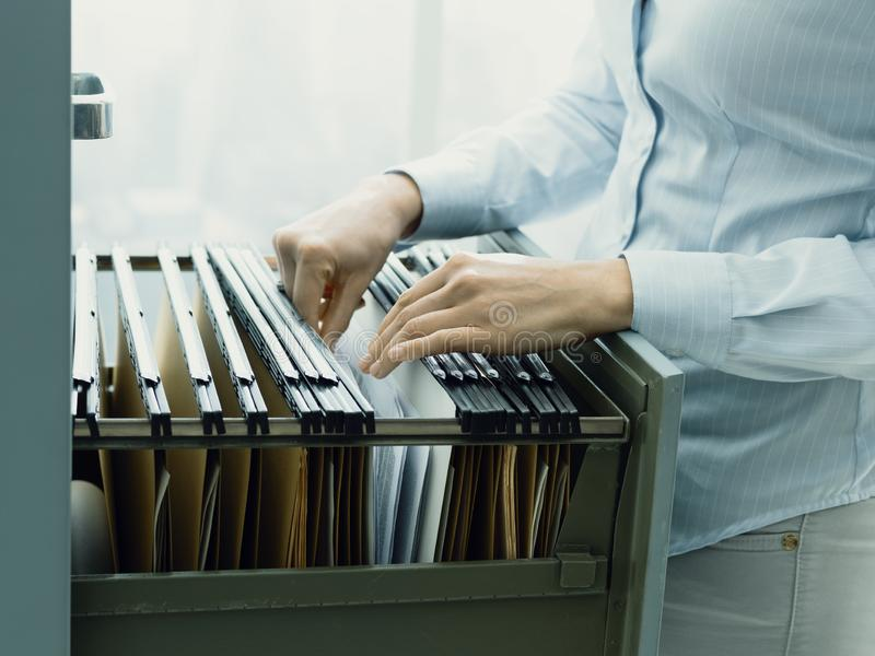 Office clerk searching files in the filing cabinet. Professional female office clerk searching files and paperwork in the filing cabinet stock images
