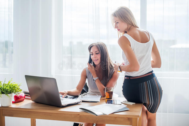 Office coffee break. Businesswoman showing. Something to colleague on laptop stock images