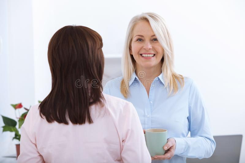 Office coffee break. Two female colleagues with cups of coffee talking. stock image