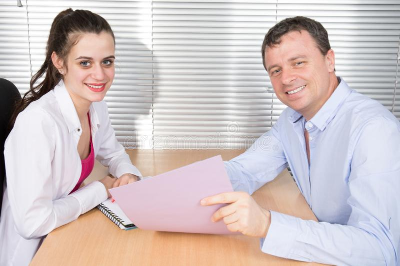 Office colleagues together look at a working folder at office desk royalty free stock image