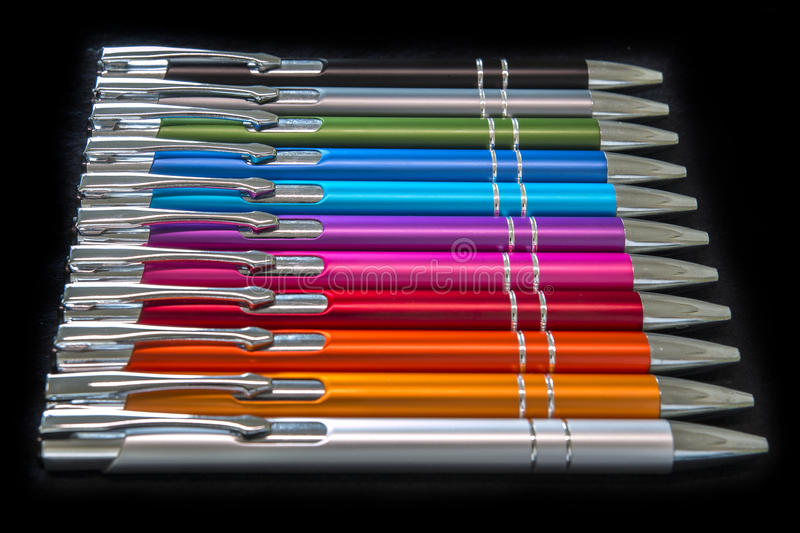 Office colored pens for kids on a black background stock image