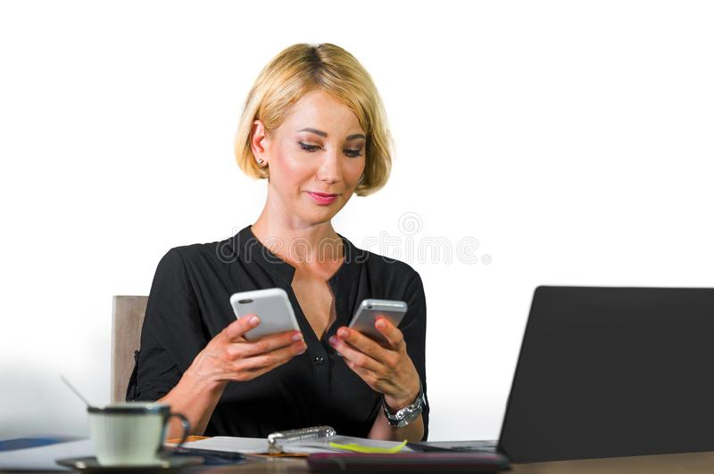 Office corporate portrait of young beautiful and happy business woman sitting at laptop computer desk busy with mobile phones conf royalty free stock image
