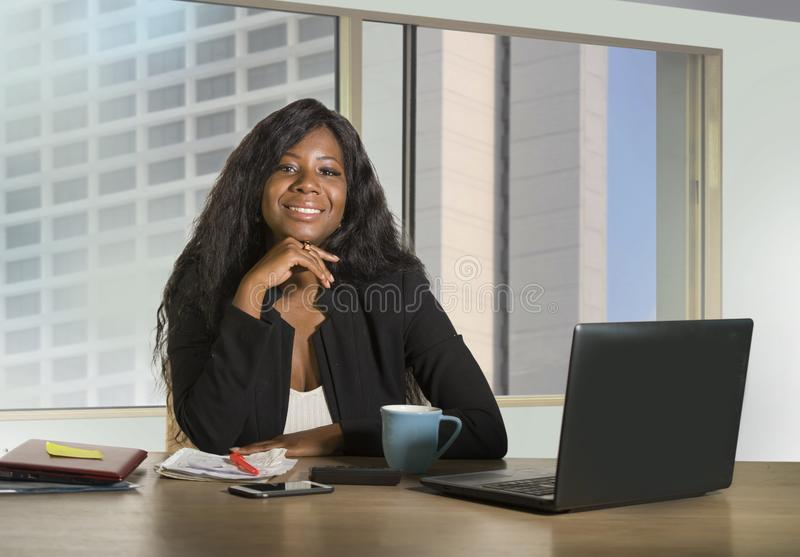 Office corporate portrait of young happy and attractive black African American businesswoman working confident at computer desk sm. Iling satisfied in financial stock photo
