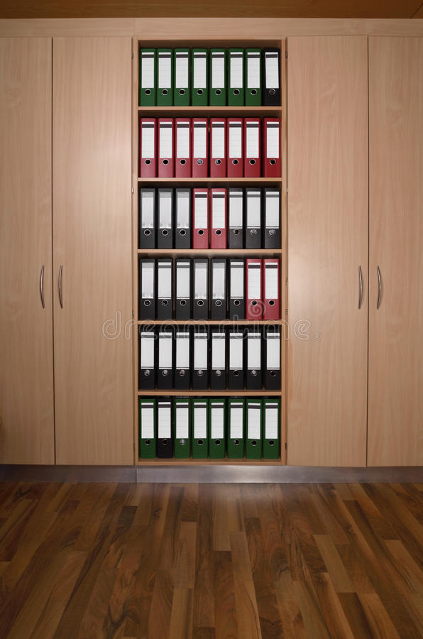 Office cupboard with folders, wooden floor royalty free stock photo