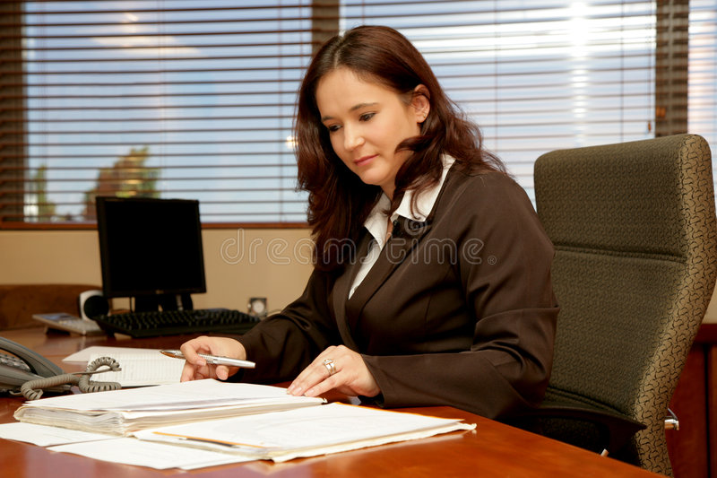 Office Desk. A woman sitting at her desk in a office stock photos