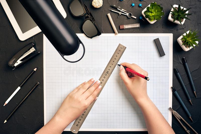 Office desk background hand with pen writing construction project ideas concept, With tablet, drawing equipment and lamp royalty free stock image